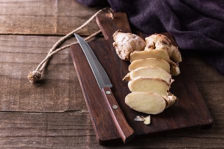 素朴な木製の背景上の作品とまな板の上のナイフで削減新鮮なショウガの根 写真素材