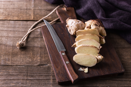 Fresh ginger root cut on the pieces and knife on a cutting board over rustic wooden background