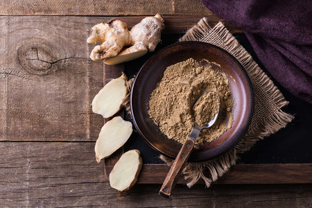 Flat lay of ground ginger in a ceramic plate and fresh ginger pieces over rustic wooden background. Top view, Copyspace Banco de Imagens