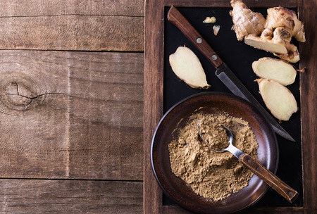Ground ginger in a ceramic plate over rustic wooden background. Top view