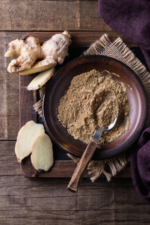 Raw and ground ginger over rustic wooden background