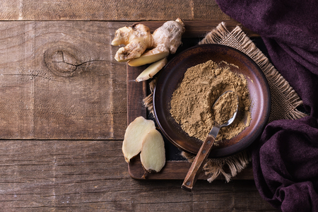 Stillife with ground ginger and fresh ginger pieces over wooden background. Top view, Copyspace Banco de Imagens