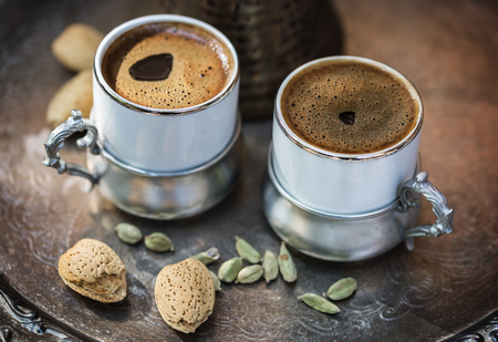Two cups of Turkish coffee in authentic coffee ware, almonds in shell and cardamom pods over silver tray. Selective focus, shallow DoF Banco de Imagens