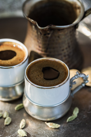 Turkish coffee in authentic cups and coffee pot on a metal tray. Selective focus, shallow DoF
