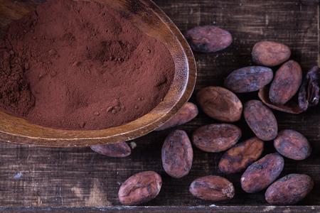カカオ パウダーと素朴な木製の背景上に生カカオ豆。上面図、クローズ アップ