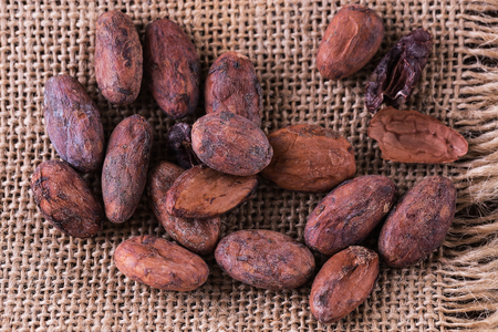Raw cacao beans on a burlap cloth background. Top view, close up Banco de Imagens