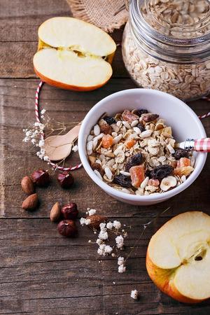 素朴な木製の背景にナッツ類、乾燥果実の健全なグルテン フリー ミューズリーのボウル。きれいに食べる、ビーガン、ベジタリアン、健康的な生活