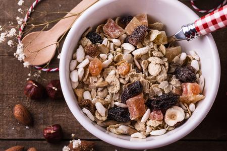 上から素朴な木製の背景上乾燥ベリーとナッツ健康グルテン無料ミューズリーのボウルのマクロの表示。きれいに食べる、健康的な生活、ビーガン