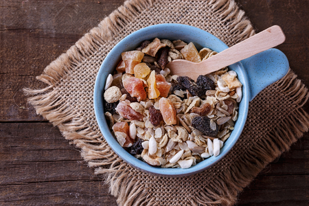 Top view image of bowl of healthy gluten free muesli with nuts and dried berries over rustic wooden background. Clean eating, Healthy living, Vegan, Vegetarian, Gluten free food concept