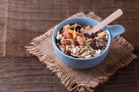 Bowl of healthy gluten free muesli with nuts, seeds and dried berries over rustic wooden background. Clean eating, Healthy living, Vegan, Vegetarian, Gluten free food concept