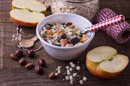 健全なグルテン フリー ミューズリー乾燥果実、アーモンドとヘーゼル ナッツ素朴な木製の背景上の白いセラミックのボウル。きれいに食べる、健