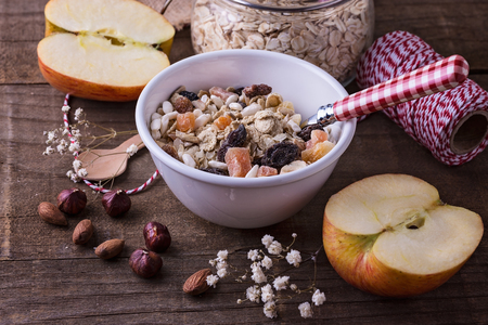 White ceramic bowl of healthy gluten free muesli with dried berries, almonds and hazelnuts over rustic wooden background. Clean eating, Healthy living, Vegan, Vegetarian, Gluten free food concept Banco de Imagens
