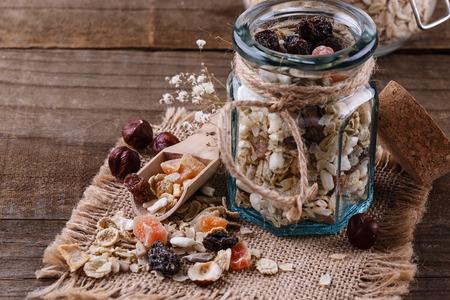 素朴な木製の背景上健全なグルテン フリー ミューズリー ナッツ、種子、乾燥果実のイメージを閉じます。きれいに食べる、健康的な生活、ビーガ