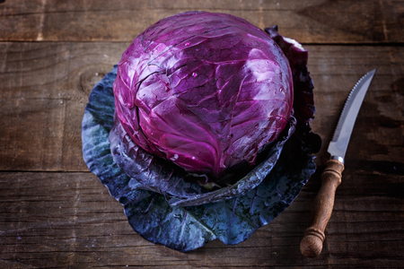Single head of Red cabbage and knife over rustic wooden background Banco de Imagens