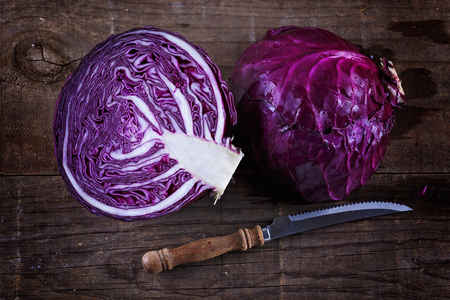 Head of Red cabbage cut in half and knife over rustic wooden background from above