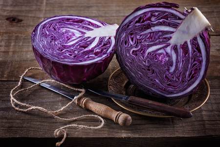 Head of Red cabbage cut in half and knives over rustic wooden background Stockfoto