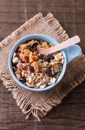 健全なグルテン フリー ミューズリー上から素朴な木製の背景にブルーのボウルにナッツと乾燥ベリーです。きれいに食べる、健康的な生活、ビーガ