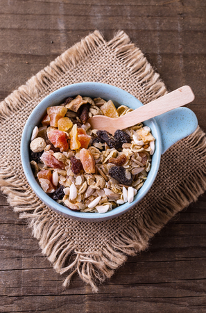 Healthy gluten free muesli with nuts and dried berry in blue bowl over rustic wooden background from above. Clean eating, Healthy living, Vegan, Vegetarian, Gluten free food concept Banco de Imagens