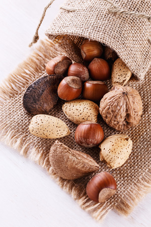 白い木製の背景にシェルでナッツの盛り合わせ。アーモンド、ブラジル ナッツ、クルミ、ヘーゼル ナッツのクローズ アップ 写真素材