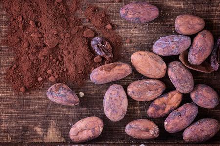 生のカカオ豆と素朴な木製の背景にココア パウダー。上面図、クローズ アップ