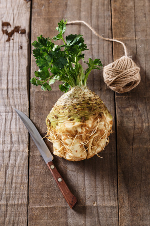 Raw fresh bulb of celeriac root and knife on rustic wooden background Banco de Imagens