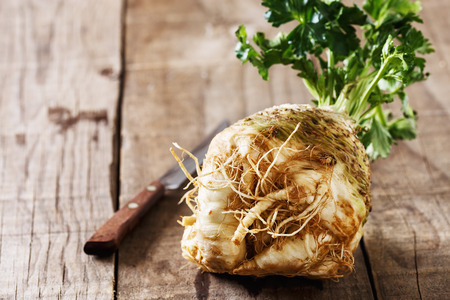 Fresh organic celeriac root on rustic wooden background close up