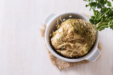 Top view image of celeriac root on white wooden background with copy space
