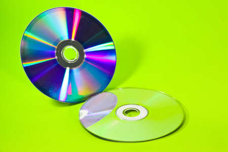 Two CDs with their mirrors in green background photo