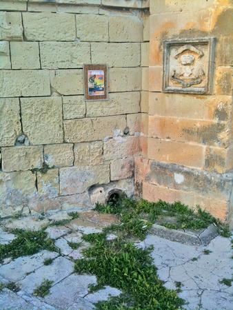 Maltese stonework, artwork, and frame on outside walls