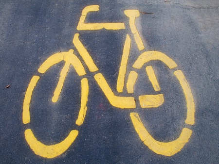 A yellow bicycle sign painted on asphalt photo