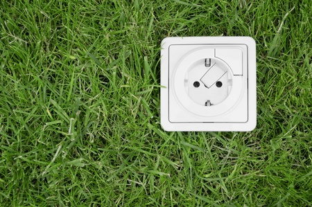 Renewable energy concept - electric outlet on grass Stock Photo - 9927535