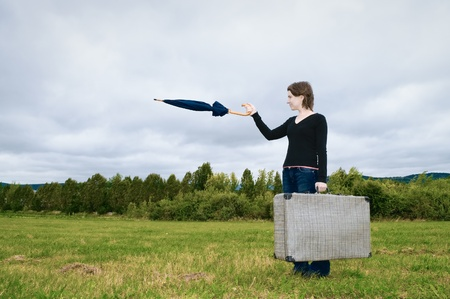 Young woman with a suitcase pointing at something with her umbrella Stock Photo - 10483258