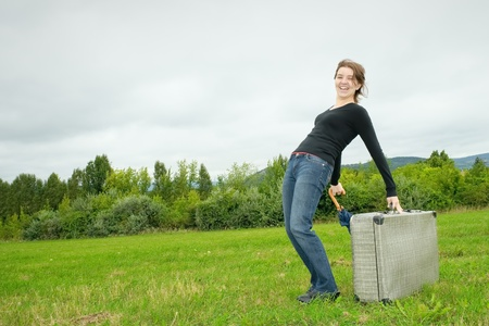 Young woman having fun with a heavy suitcase Stock Photo - 10596580