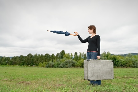 Traveler with a suitcase pointing at something with her umbrella photo