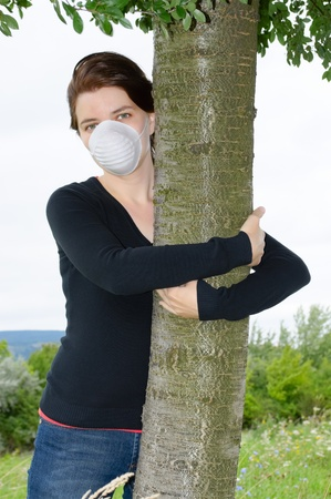 Young environmentalist in face mask hugging a tree photo