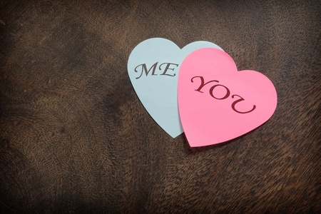 Heart shaped post its on wooden background photo