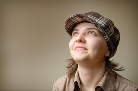 people looking up: Portrait of a young woman smiling in checked cap