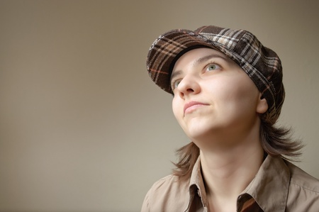 Young green eyed woman daydreaming in checked cap Stock Photo - 12376026
