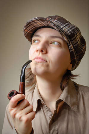 Young nicotine addict woman smoking a pipe photo