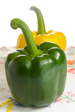 Green and yellow sweet peppers on embroidered tablecloth Stock Photo - 13234764