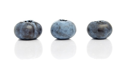 Three blueberries with reflection isolated on white background Foto de archivo