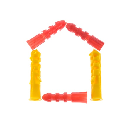 Plastic dowels in the shape of a house isolated on white background photo