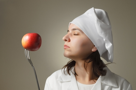 Chef woman enjoying the smell of an apple Stock Photo - 16640736