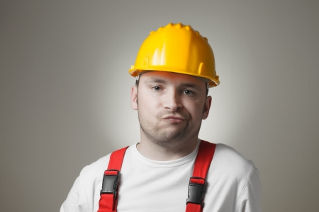maintenance fitter: Unhappy young handyman with yellow hard hat Stock Photo