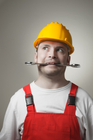 Crazy young handyman with yellow hard hat