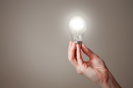 save electricity: Hand holding a glowing light bulb