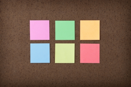 Six colorful sticky notes on fiberboard background