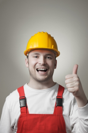 Happy young handyman with yellow hard hat photo
