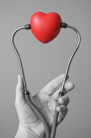 Man s hand holding a red heart and stethoscope photo