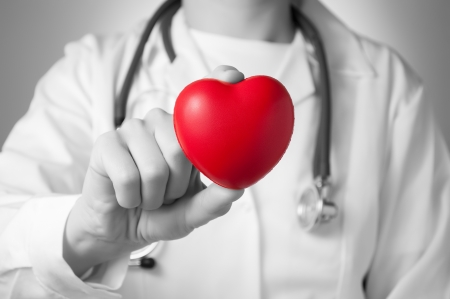 cure prevention: Red heart in the hand of a doctor Stock Photo